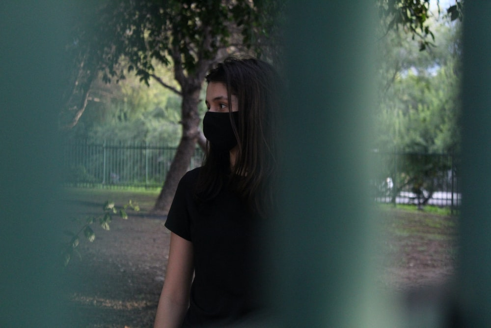 woman in black t-shirt standing near green tree during daytime