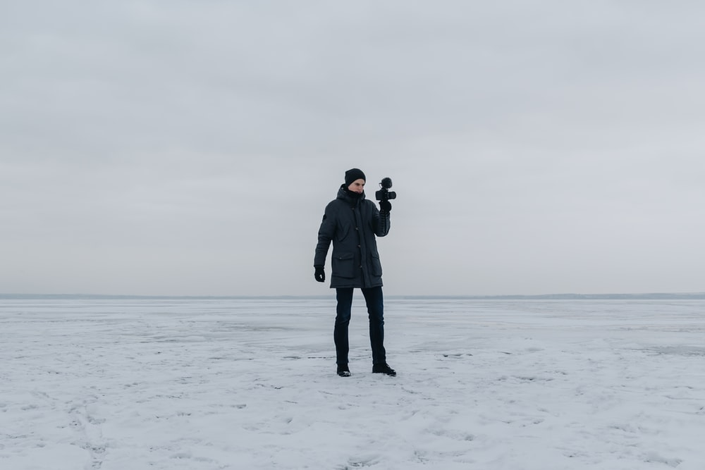man in black coat holding camera standing on snow covered ground during daytime