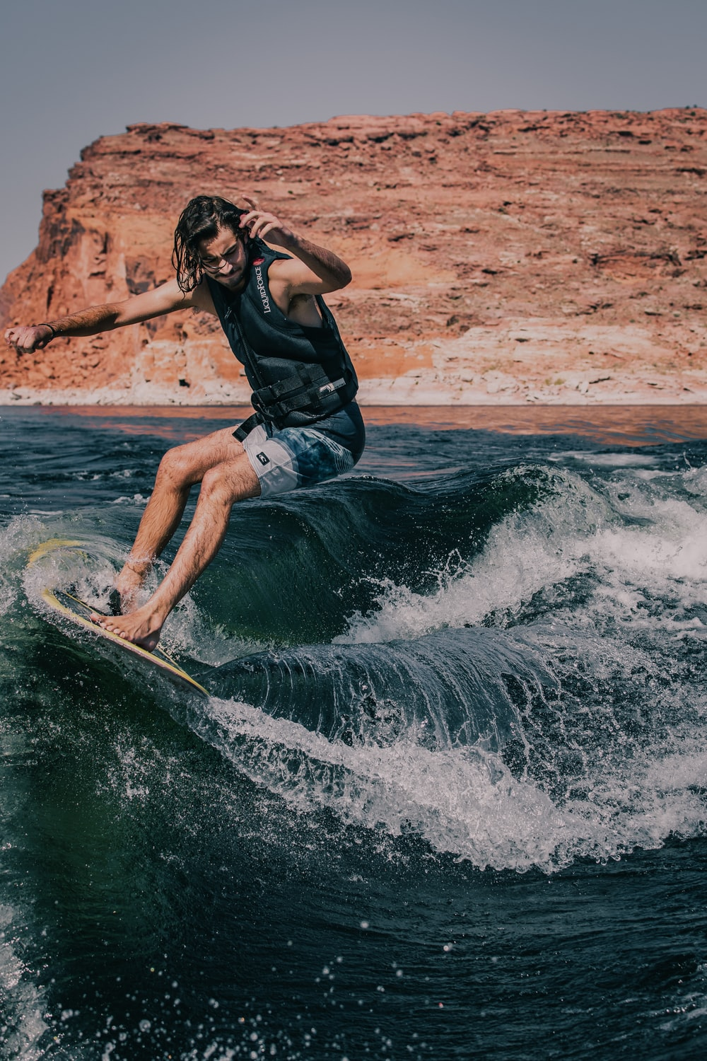 woman in black shirt and blue denim shorts surfing on water waves during daytime
