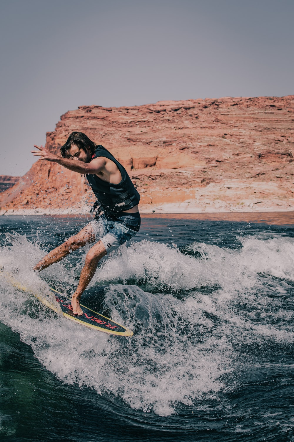 man in black tank top and blue denim shorts surfing on sea waves during daytime