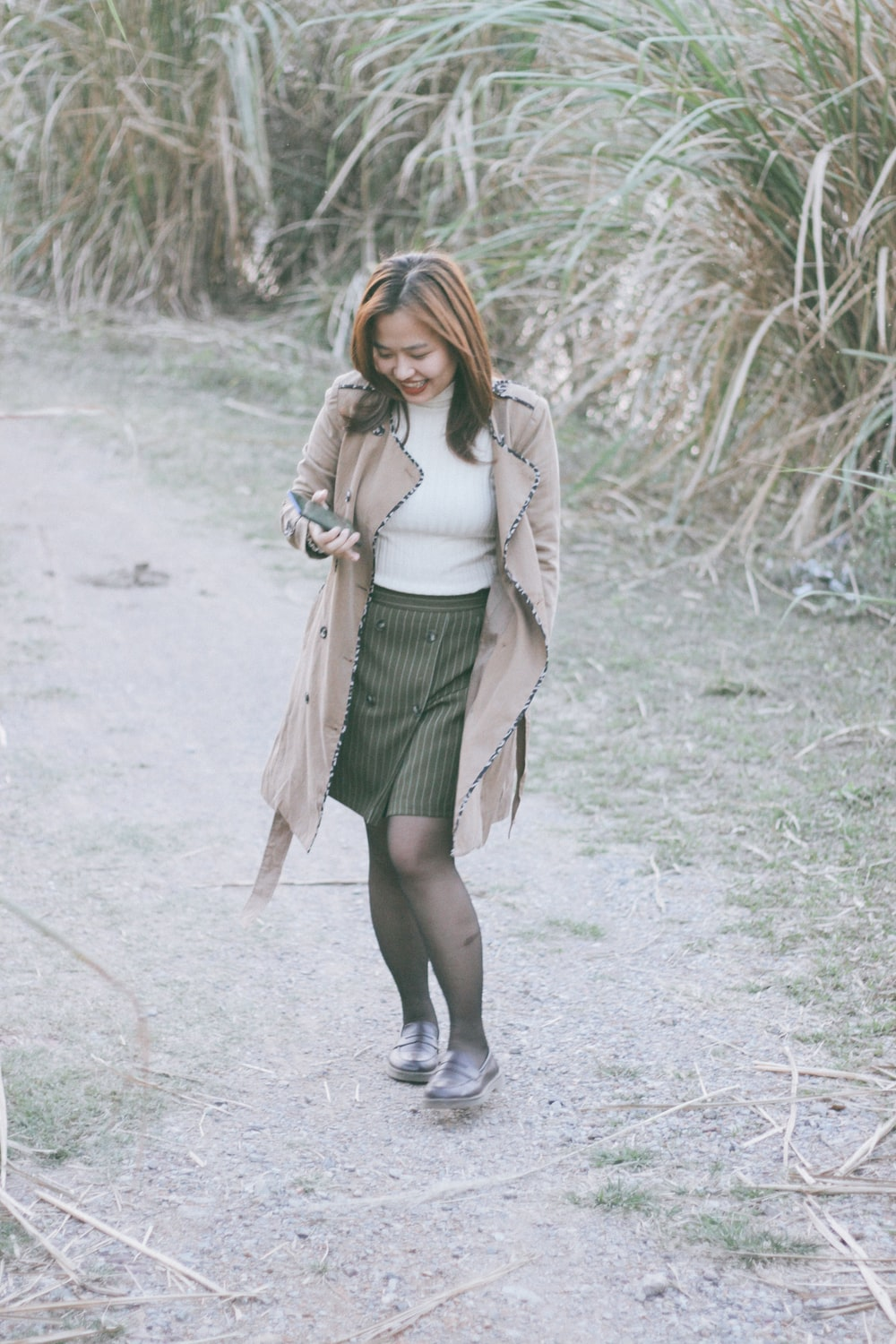 woman in white long sleeve shirt and green skirt standing on gray concrete pavement during daytime