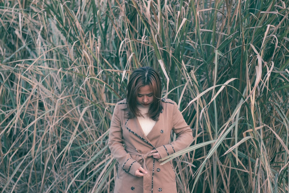 woman in brown coat standing on green grass field during daytime