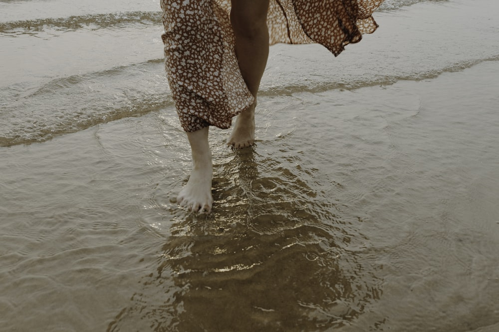 woman in red and white floral dress walking on beach during daytime