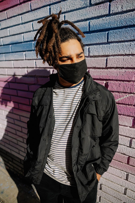 man in black leather jacket standing beside brick wall