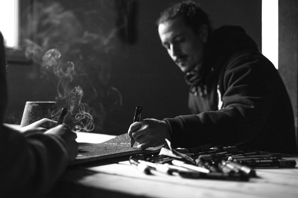 man in black jacket holding pen