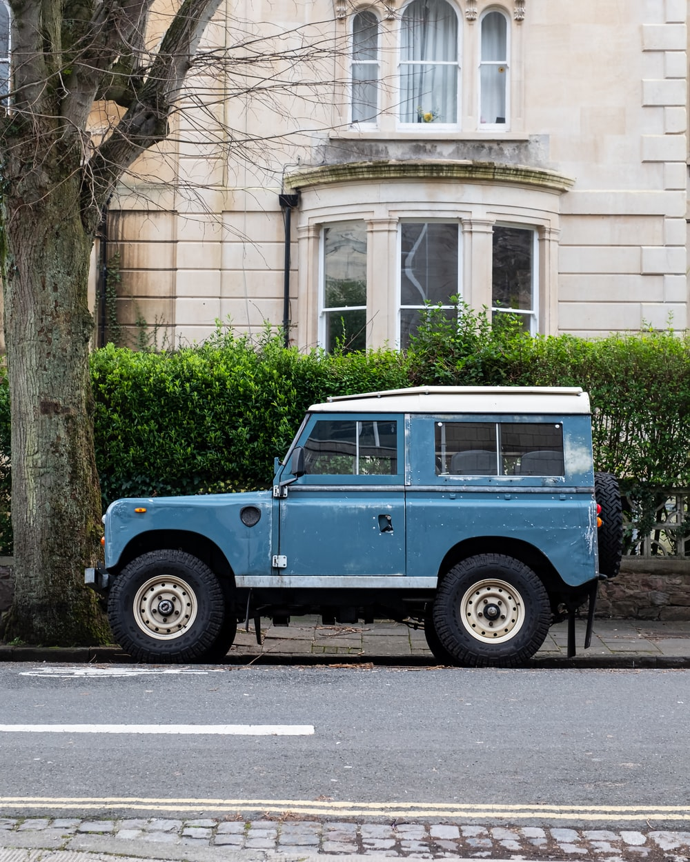 blue and white jeep wrangler parked beside brown concrete building during daytime
