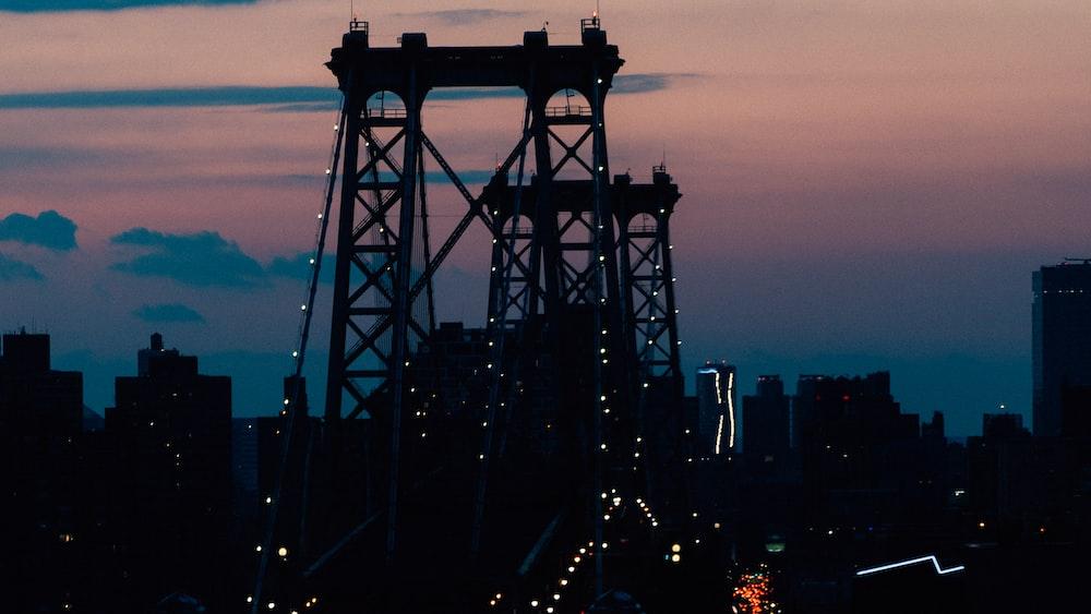 silhouette of people walking on bridge during night time