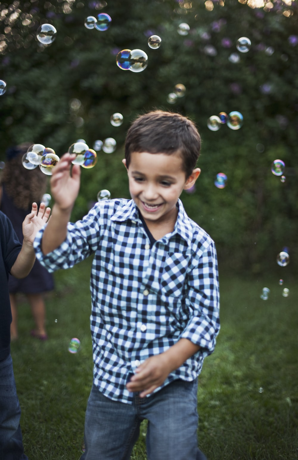 boy in blue and white plaid dress shirt playing bubbles