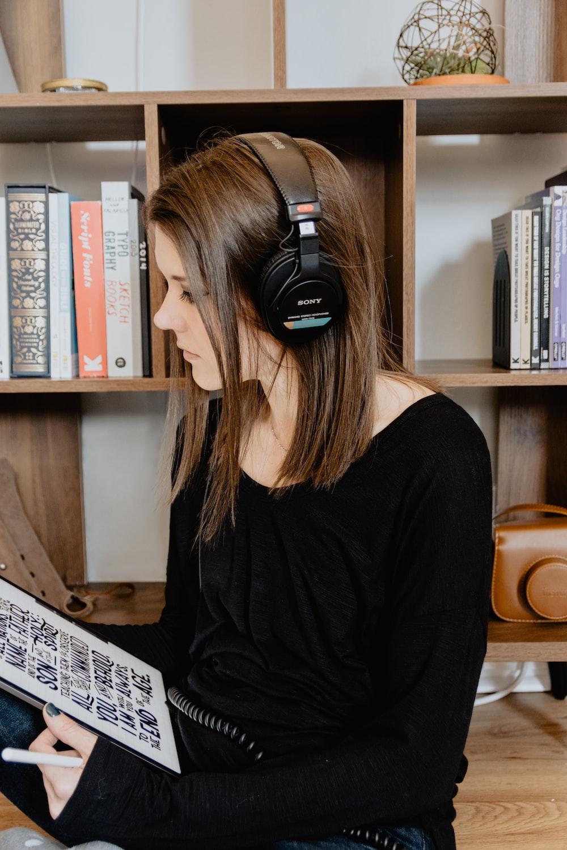 woman in black long sleeve shirt wearing black headphones