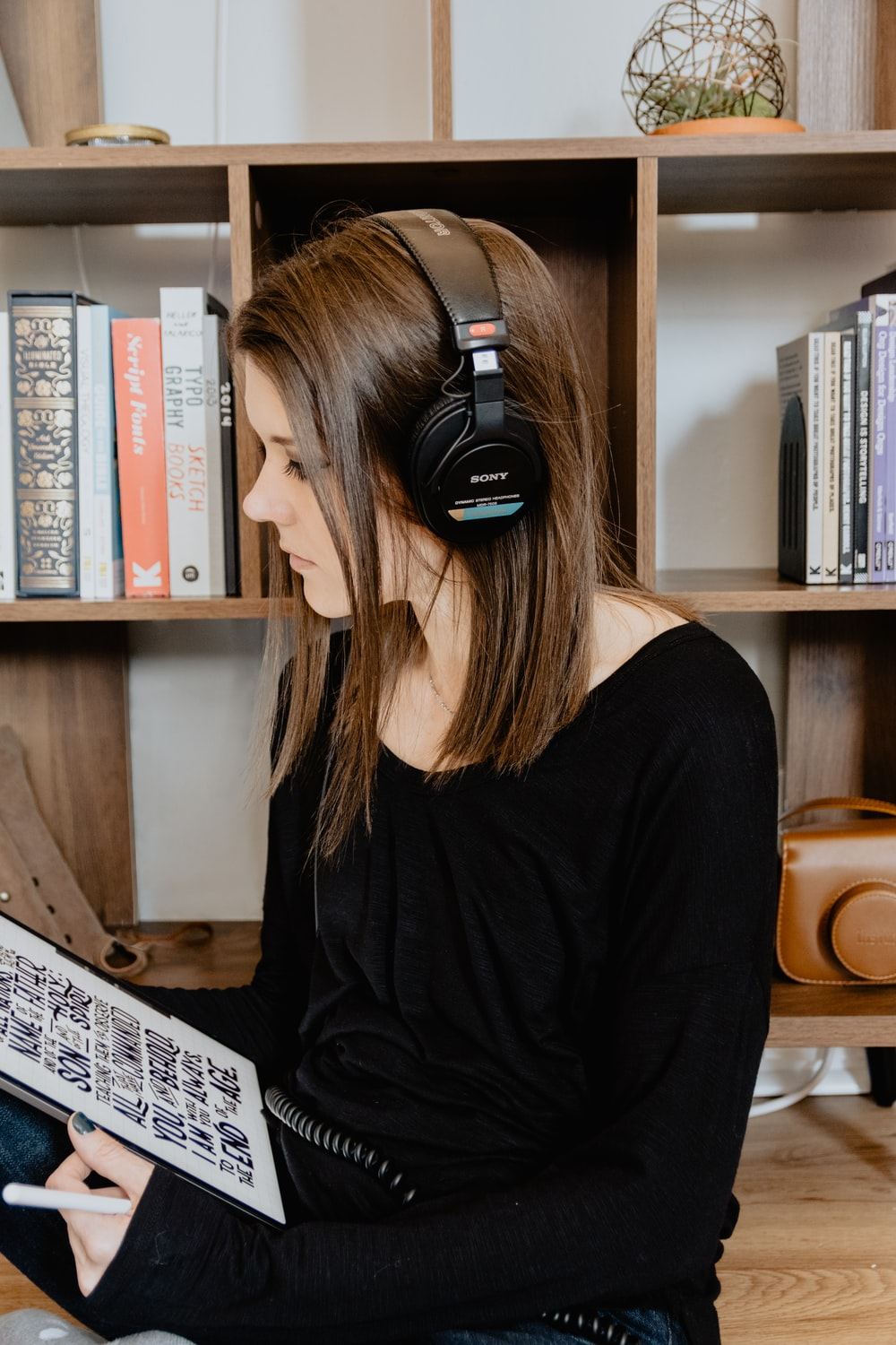woman in black long sleeve shirt wearing black headphones