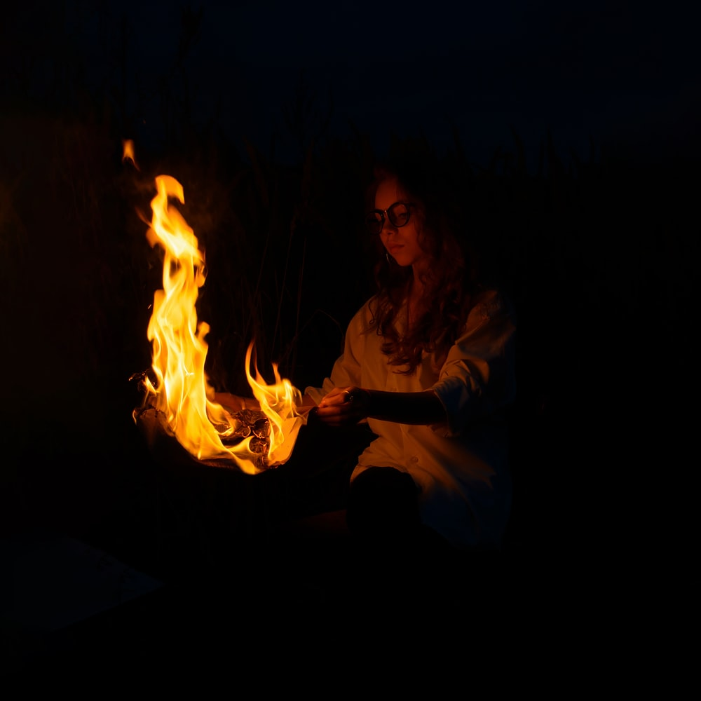 woman in white long sleeve shirt sitting on floor with fire