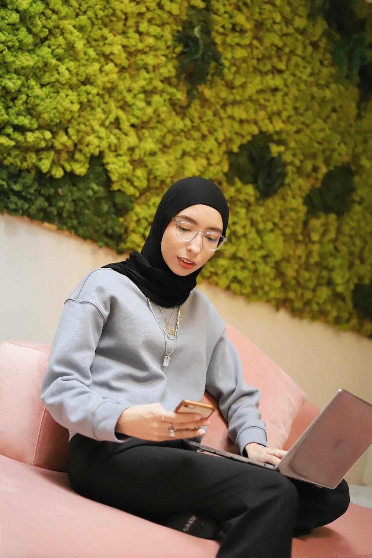 woman in black hijab using silver ipad