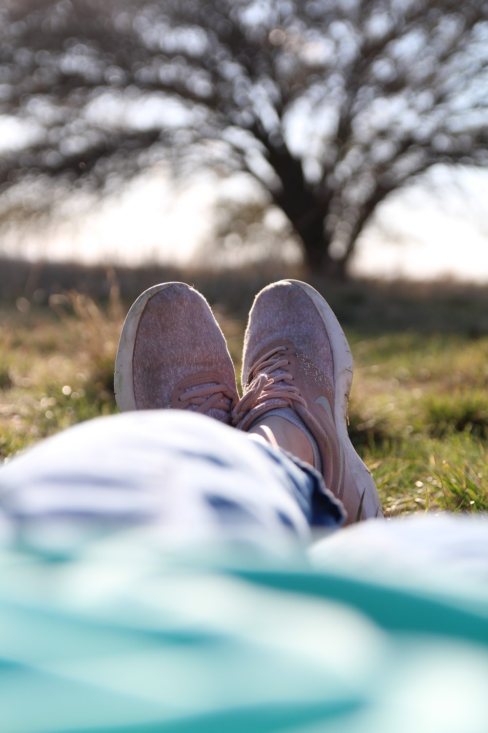 person in brown shoes sitting on green grass field during daytime