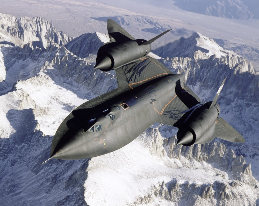 gray fighter jet flying over the mountain