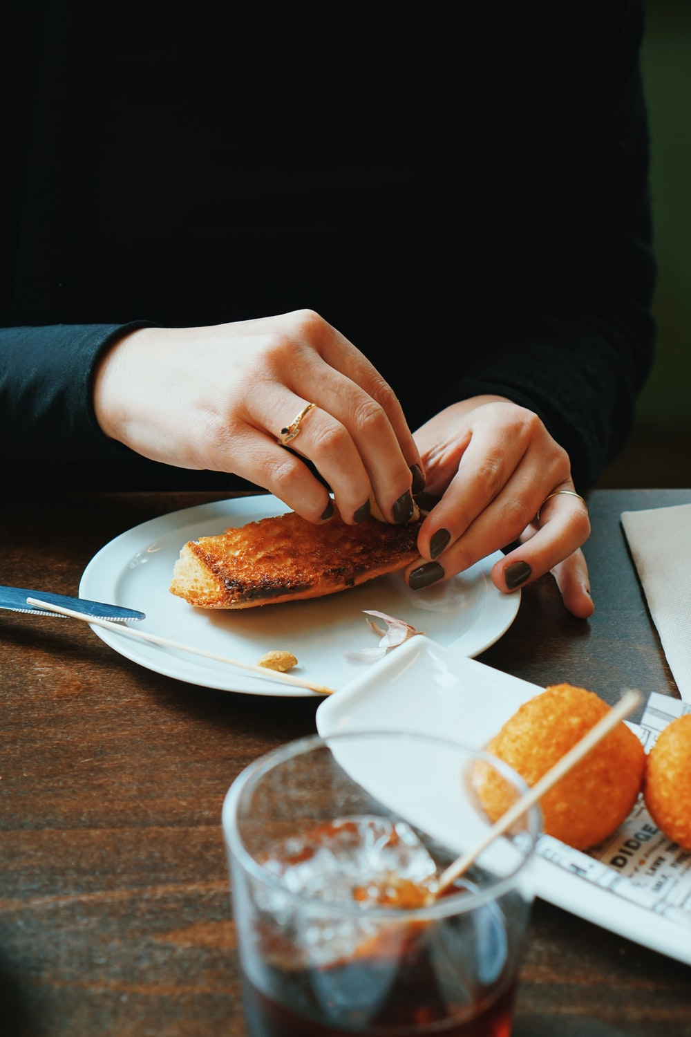 person holding sliced of bread on white ceramic plate