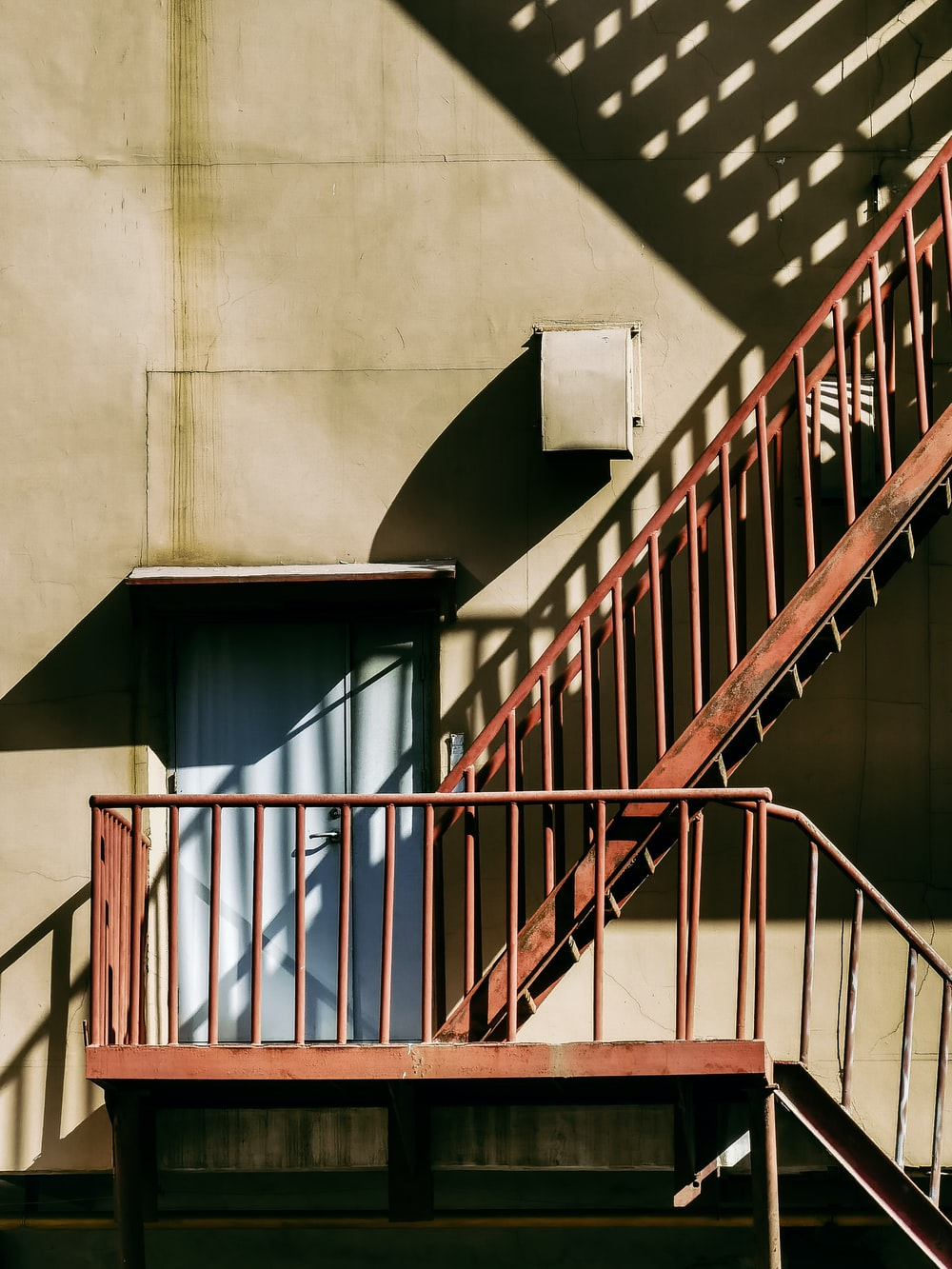 white concrete staircase with brown metal railings