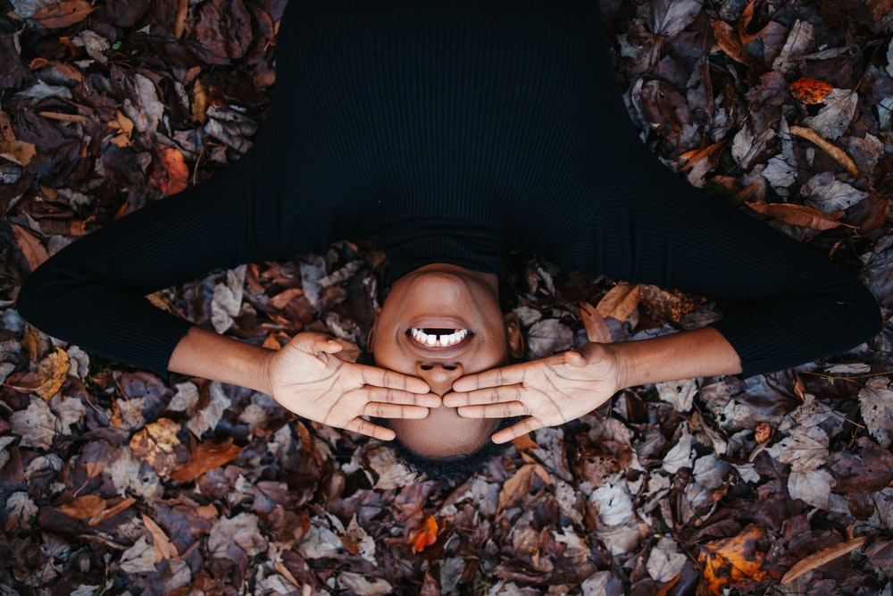 woman in black long sleeve shirt lying on dried leaves