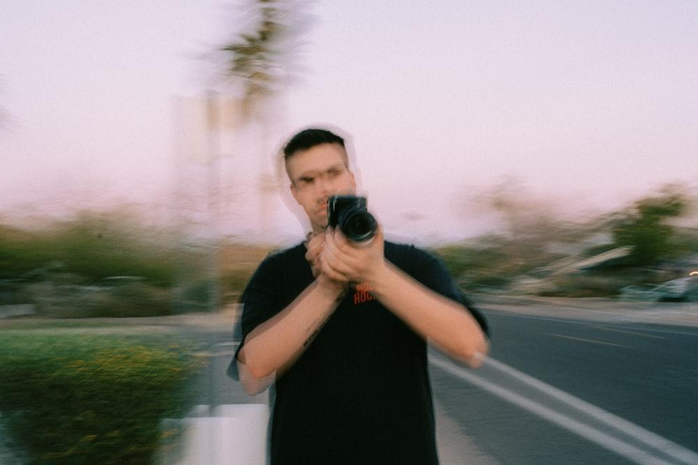 man in black tank top holding black camera