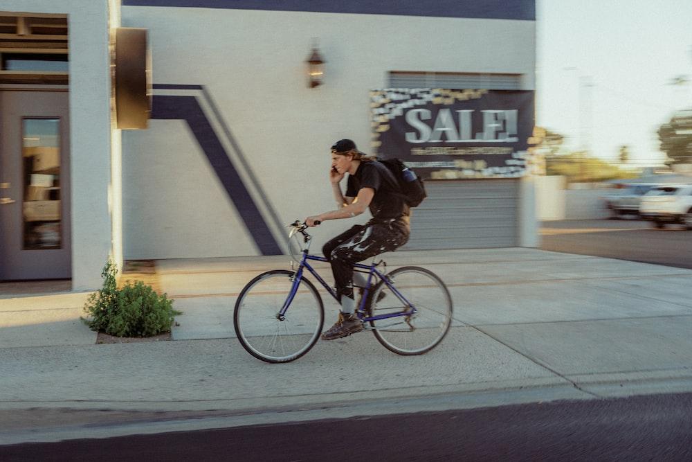man in black t-shirt riding on black bicycle during daytime