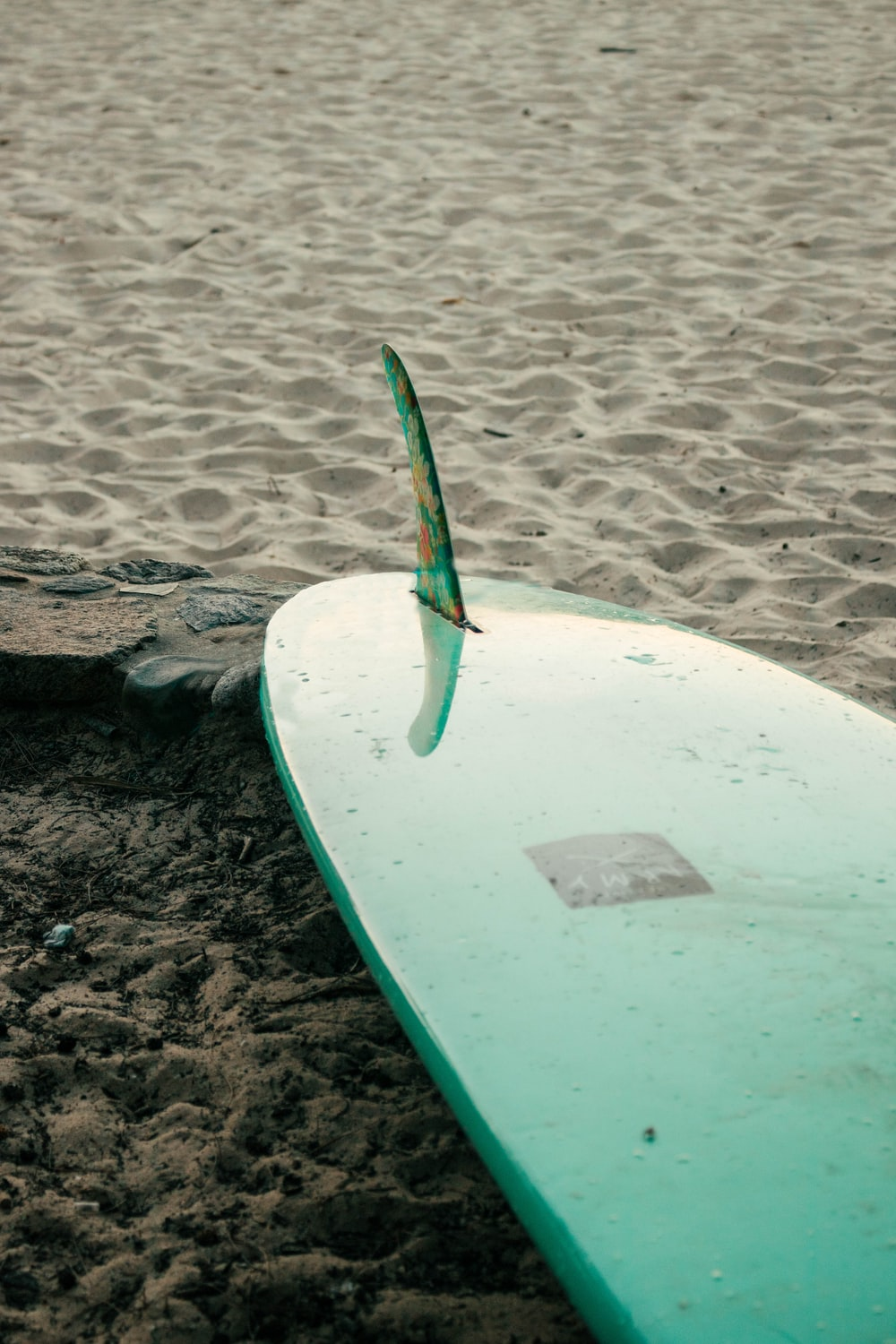 green and white surfboard on brown sand