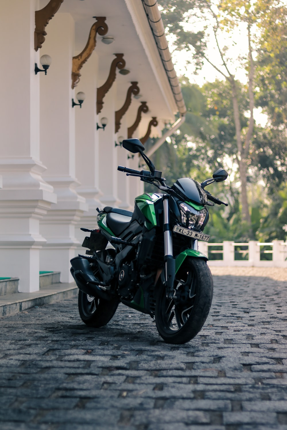 black and green naked motorcycle parked beside white building during daytime