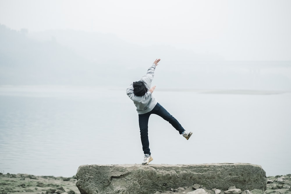 man in gray hoodie and blue denim jeans jumping on brown rock