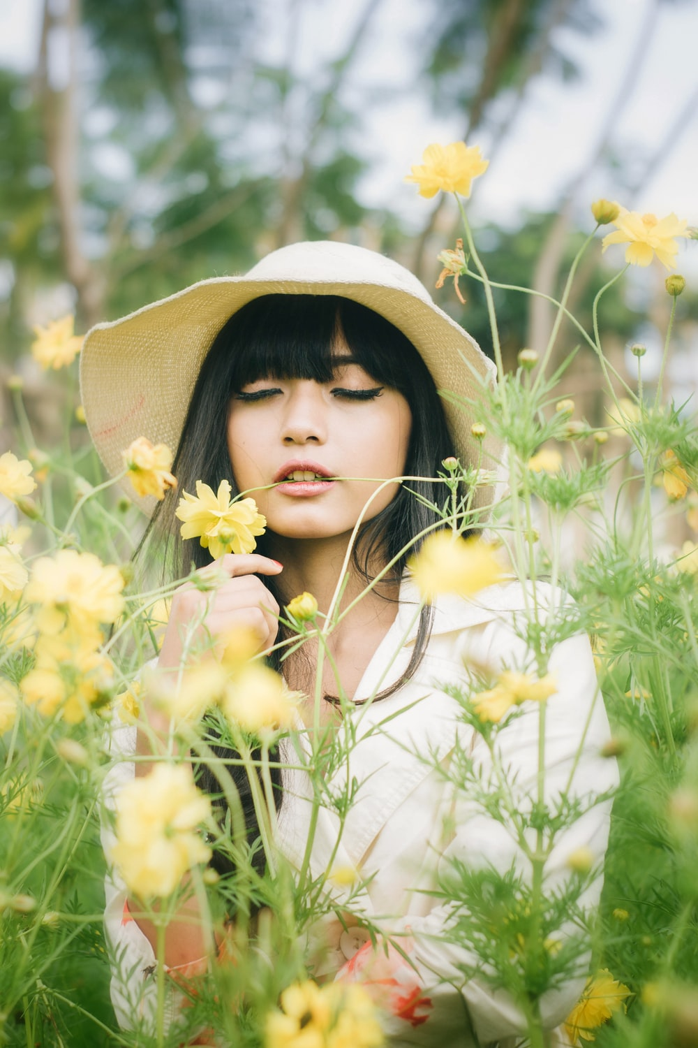 woman in white long sleeve shirt wearing brown sun hat standing on yellow flower field during