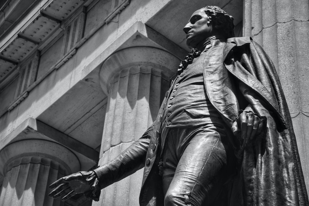 grayscale photo of man in jacket and pants statue