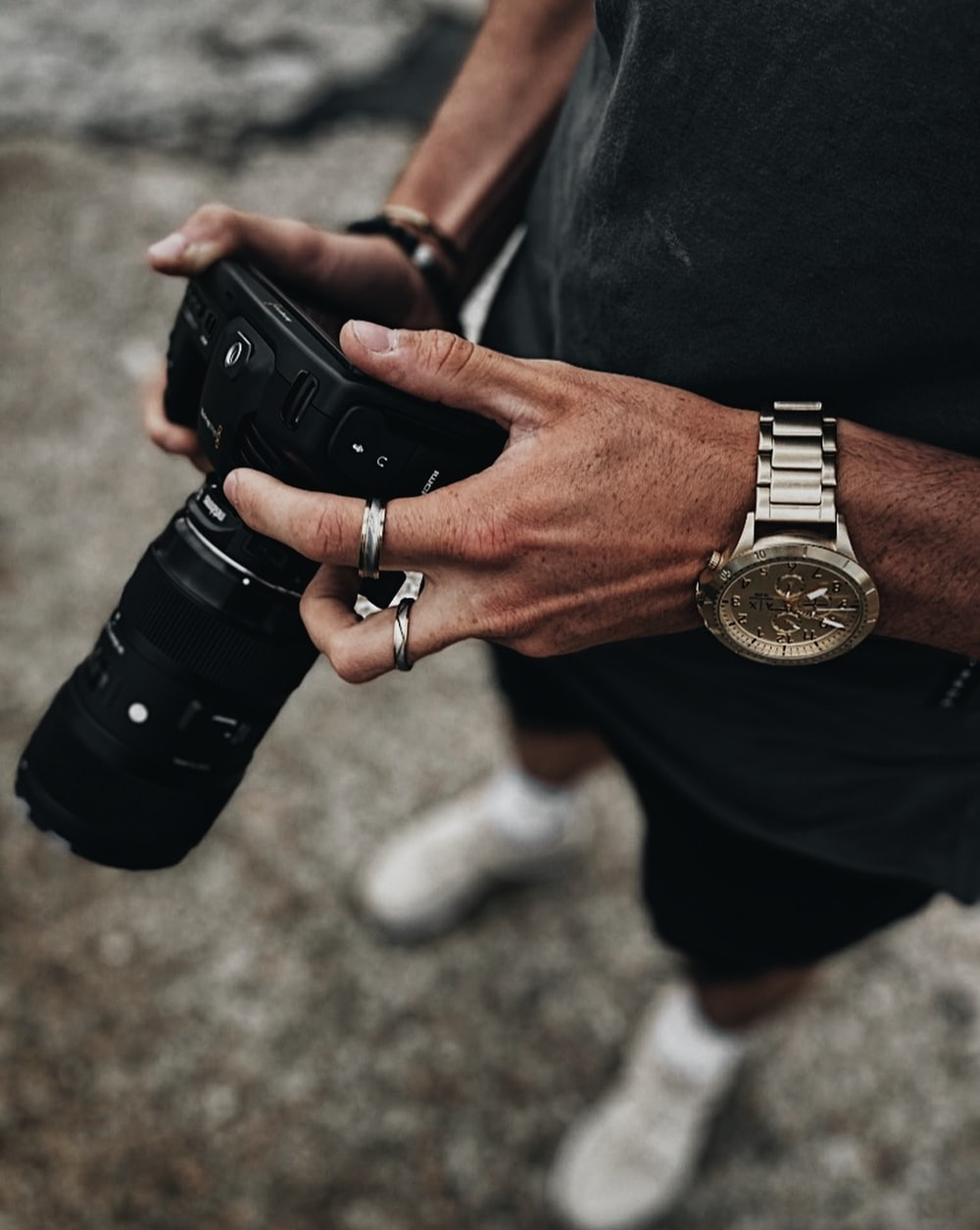 person wearing black leather strap gold round analog watch