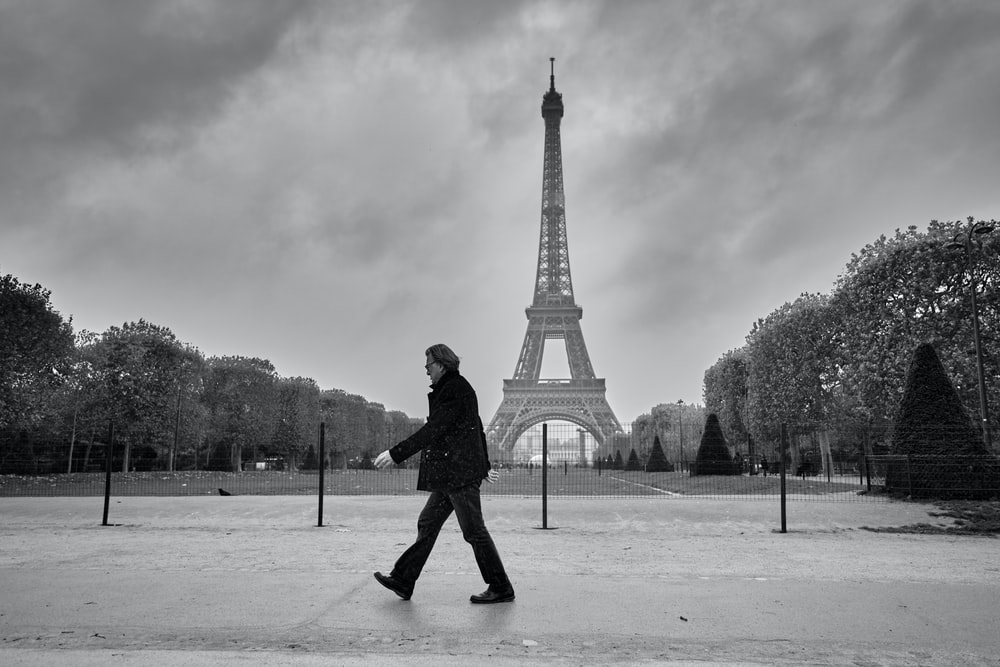 man in black jacket and pants walking on snow covered ground near eiffel tower in grayscale