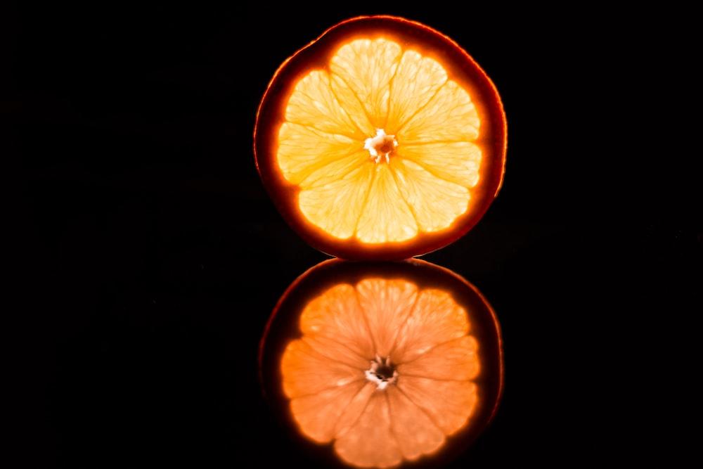 sliced orange fruit on black background