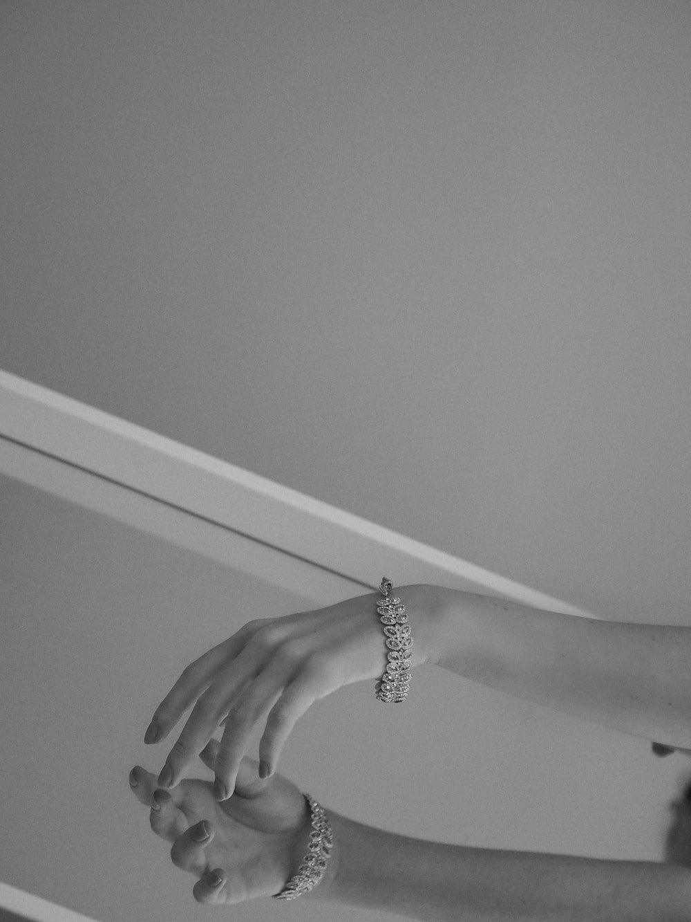grayscale photo of person wearing silver ring