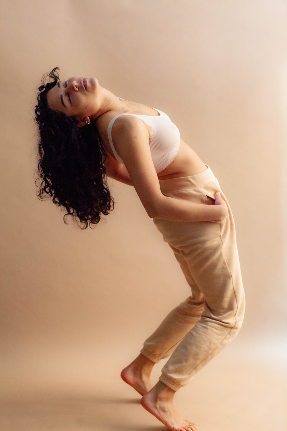 woman in white tank top and beige pants