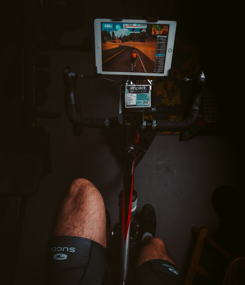person in black shorts sitting on black and red stationary bike