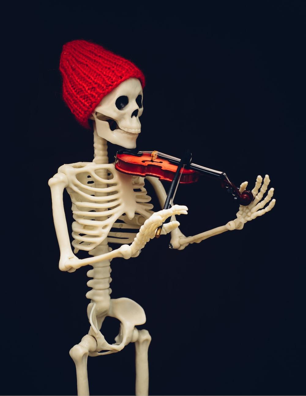 white skeleton holding brown violin