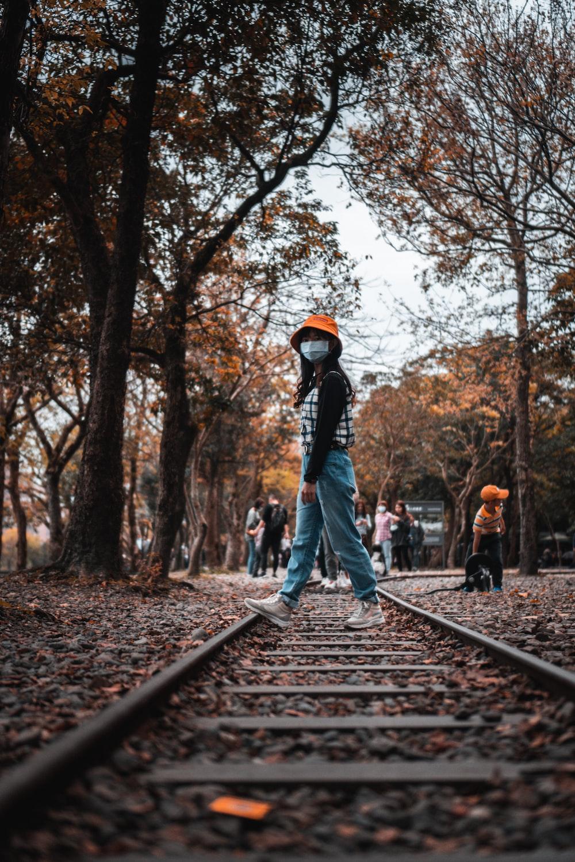 man in black jacket and blue denim jeans walking on train rail during daytime