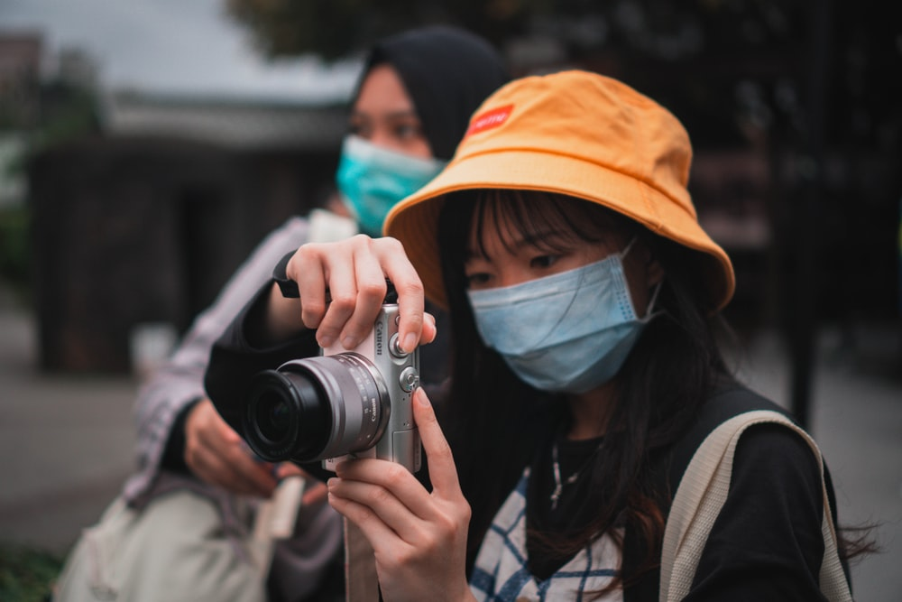 woman in brown jacket holding black camera