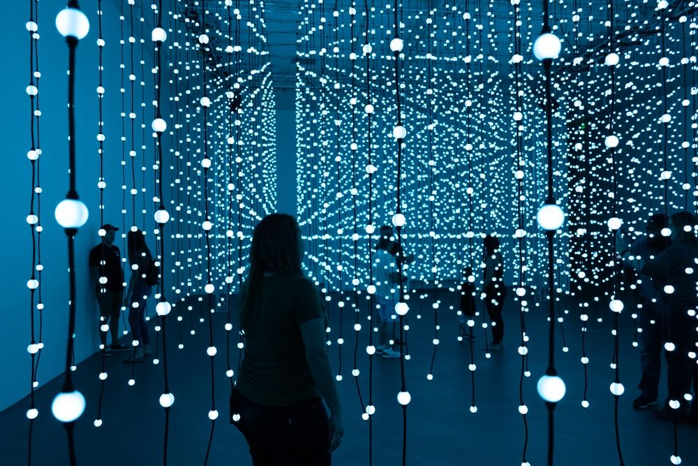 silhouette of woman standing in front of blue lights
