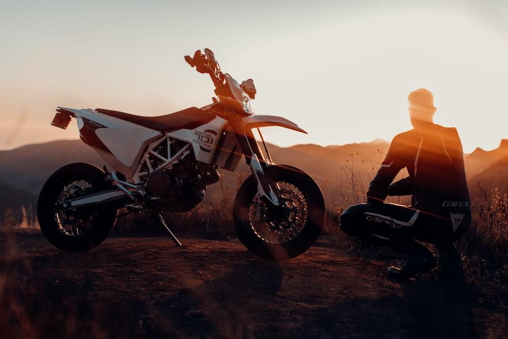 man in black jacket sitting on motorcycle during sunset