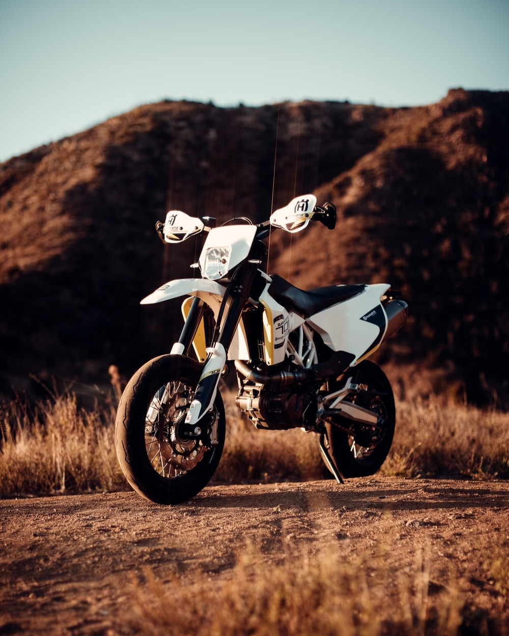 white and black sports bike on brown grass field during daytime