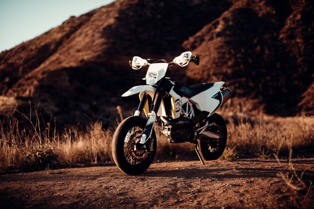 white and black sports bike on brown field during daytime
