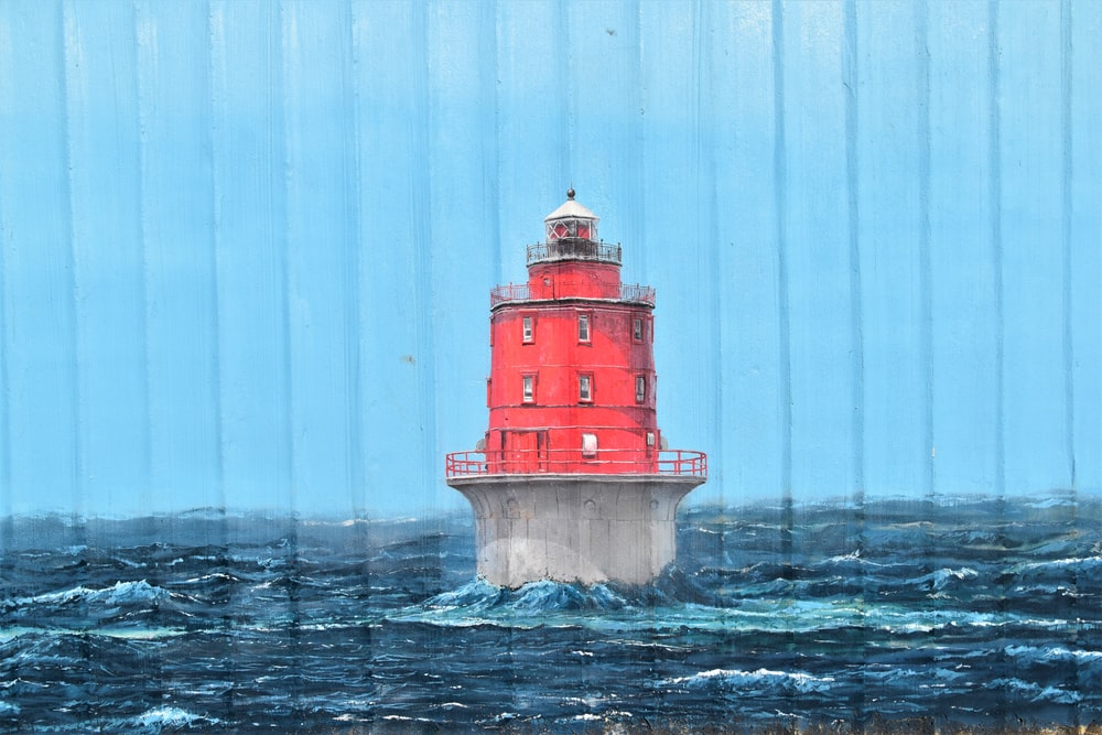 red and white lighthouse on body of water during daytime