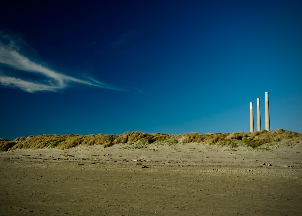 white and brown lighthouse on brown sand under blue sky during daytime