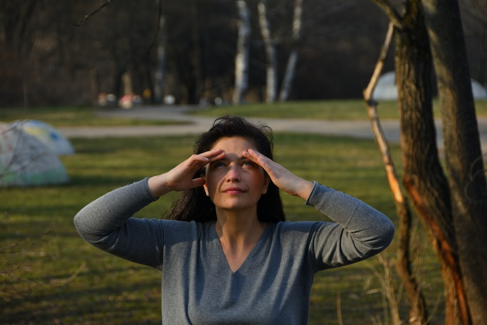 woman in blue v neck long sleeve shirt covering her face with her hands
