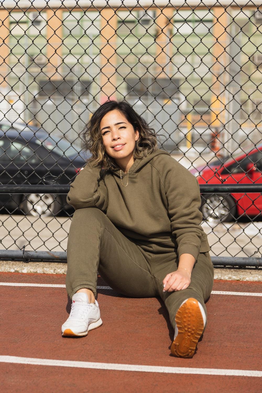 woman in brown hoodie sitting on brown concrete floor