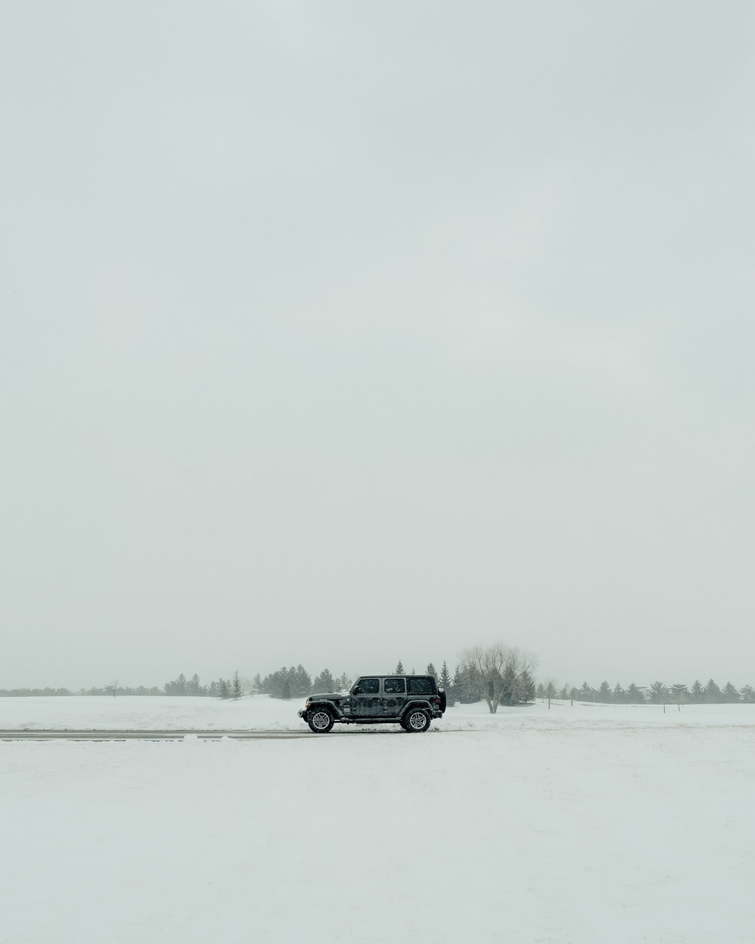 black suv on snow covered field during daytime