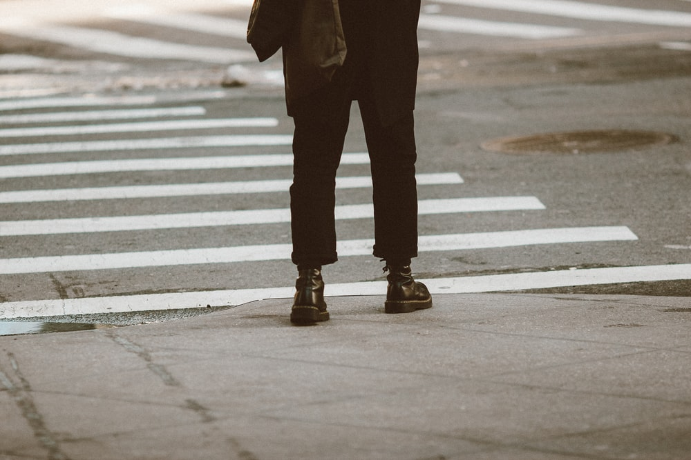 person in black pants and black boots standing on pedestrian lane during daytime