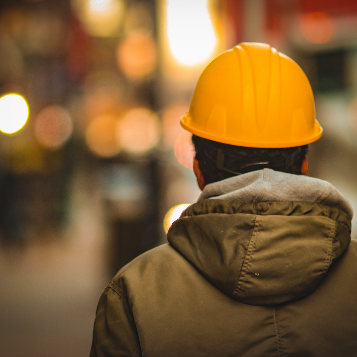person in yellow hard hat and brown jacket