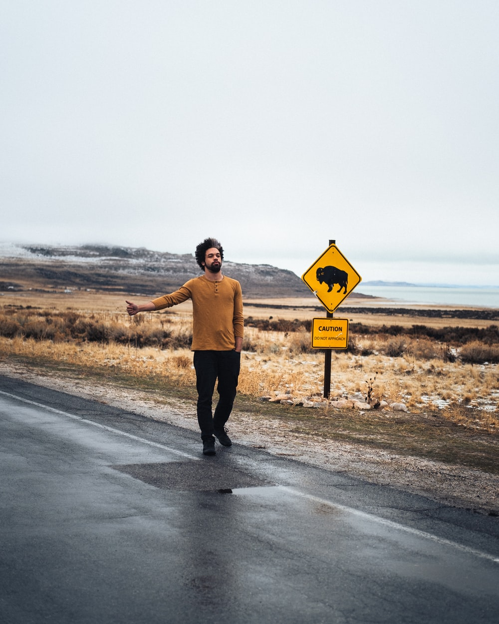 man in brown shirt and black pants standing on road