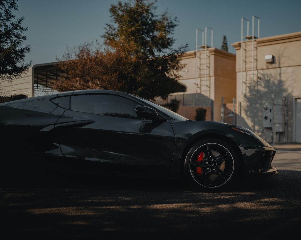 black coupe parked near brown building during daytime